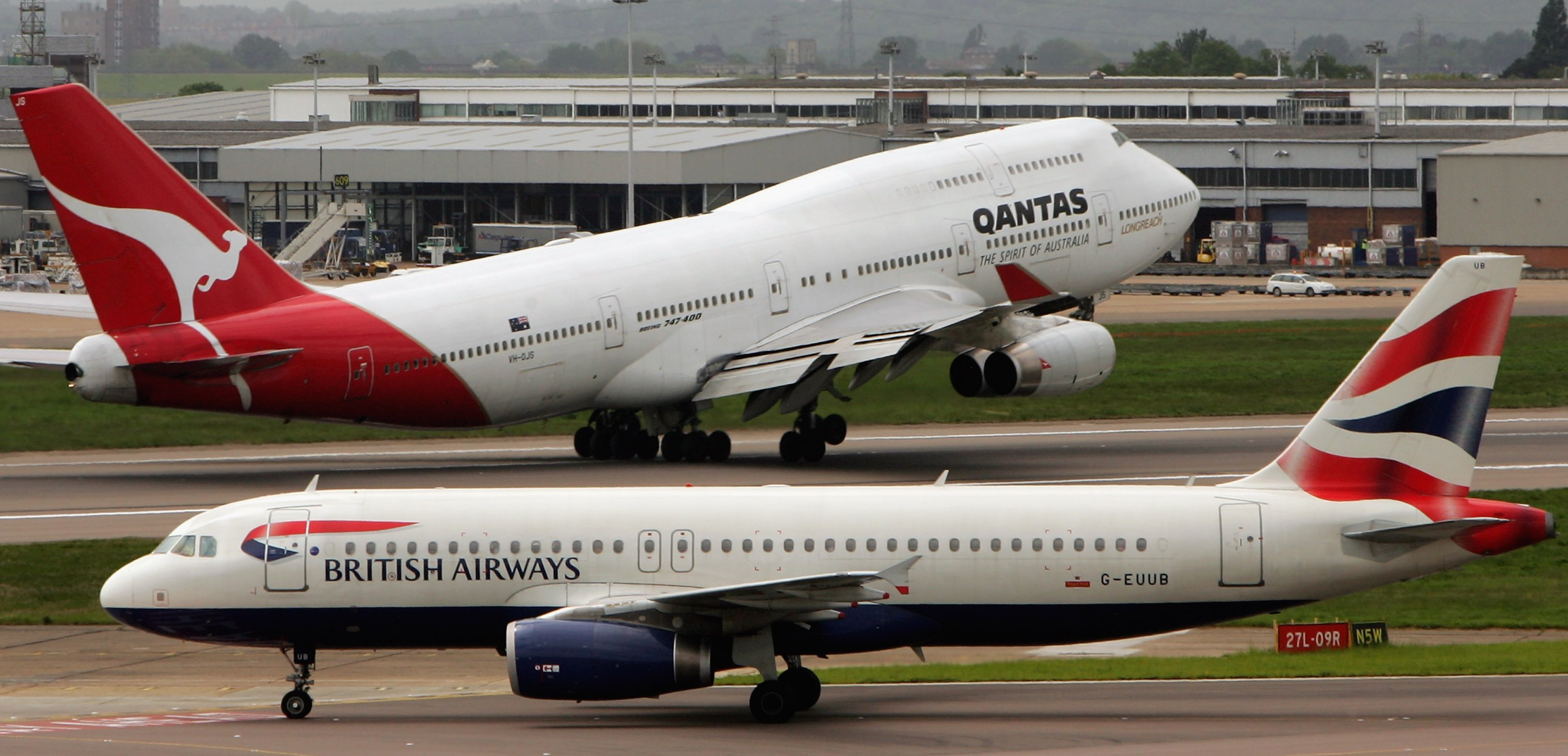 LONDON - MAY 18:  A Qantas aircraft takes off as a British Airways aircratf taxis down the runway at London Heathrow Airport on May 18, 2006 in London, England. Heathrow consists of four passenger terminals and is responsible for around half a million takeoffs/landings and transporting around 65 million passengers every year. (Photo by Scott Barbour/Getty Images)