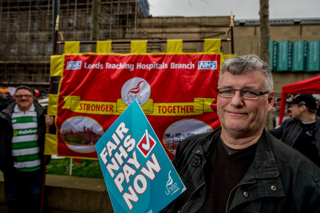 Leeds April 1st 2017. Wilson Tweed, Branch Secretary Leeds Teaching Hospital in front of the new branch banner designed by Paul Brown. Approximately a 1000 campaigners fighting to save the NHS attended a march & rally in Leeds city centre, Yorkshire