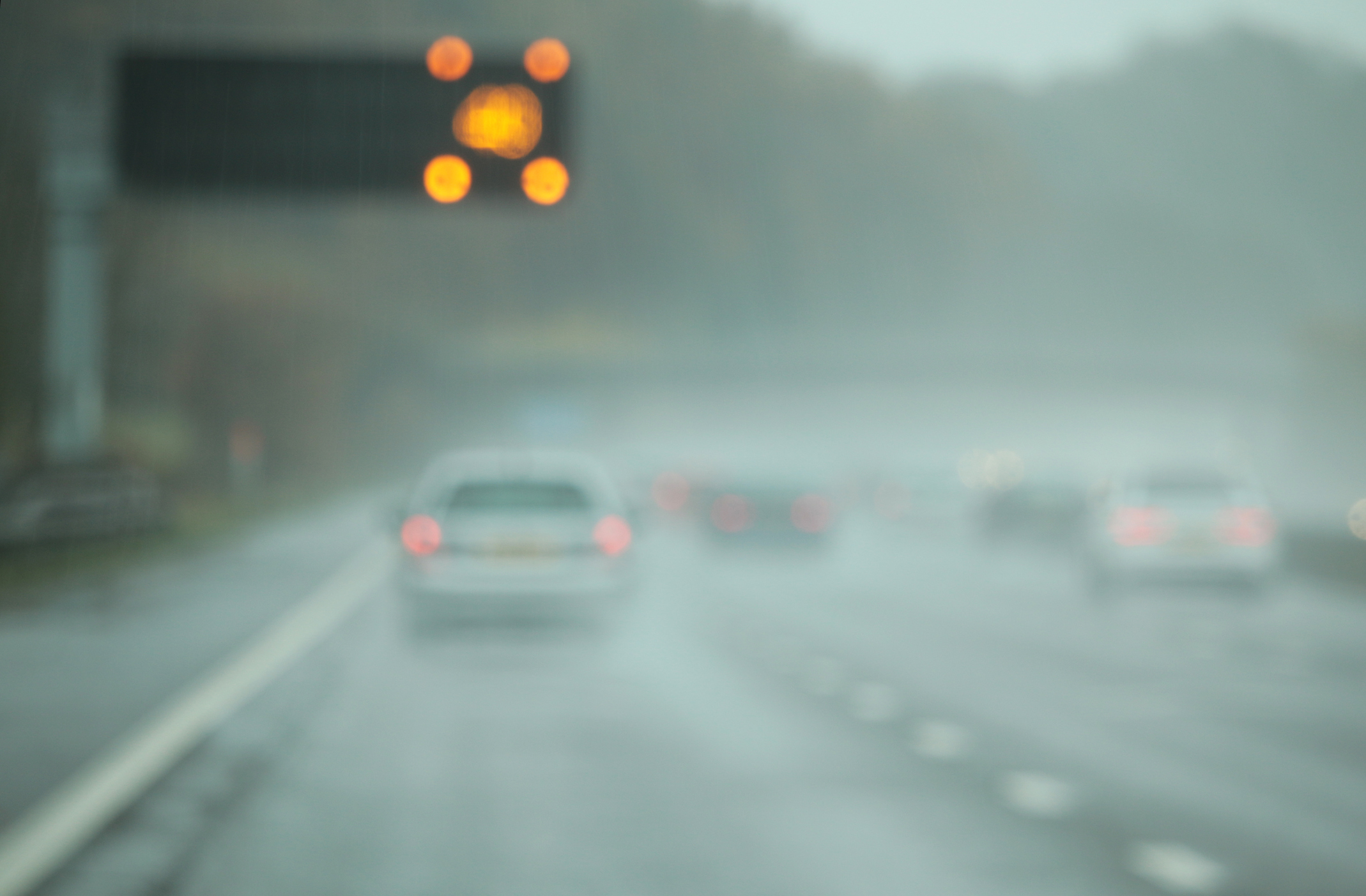 The M6 motorway in England on a wet November day, with speed warning lights flashing overhead. Defocused to highlight poor visibility.