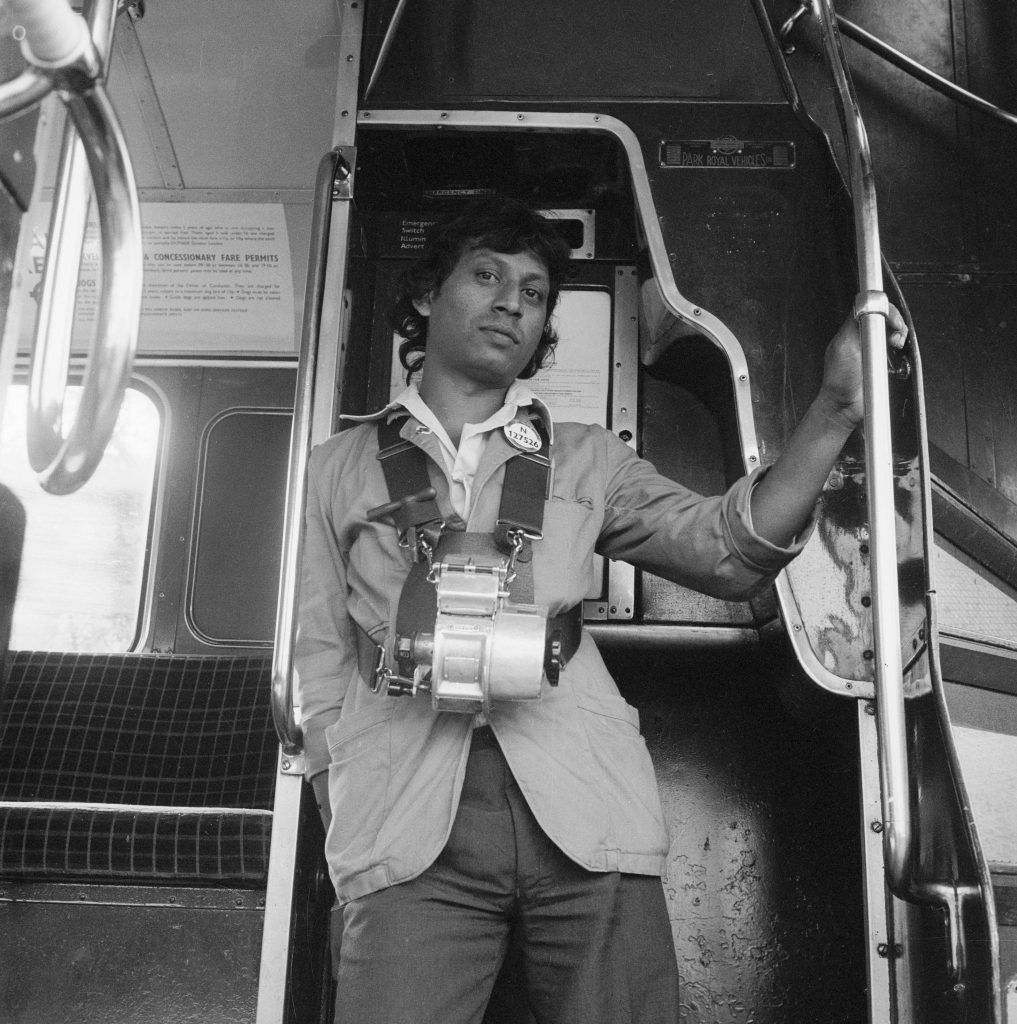 A London Transport bus conductor. An Asian London Transport bus conductor, between 1976-1980.