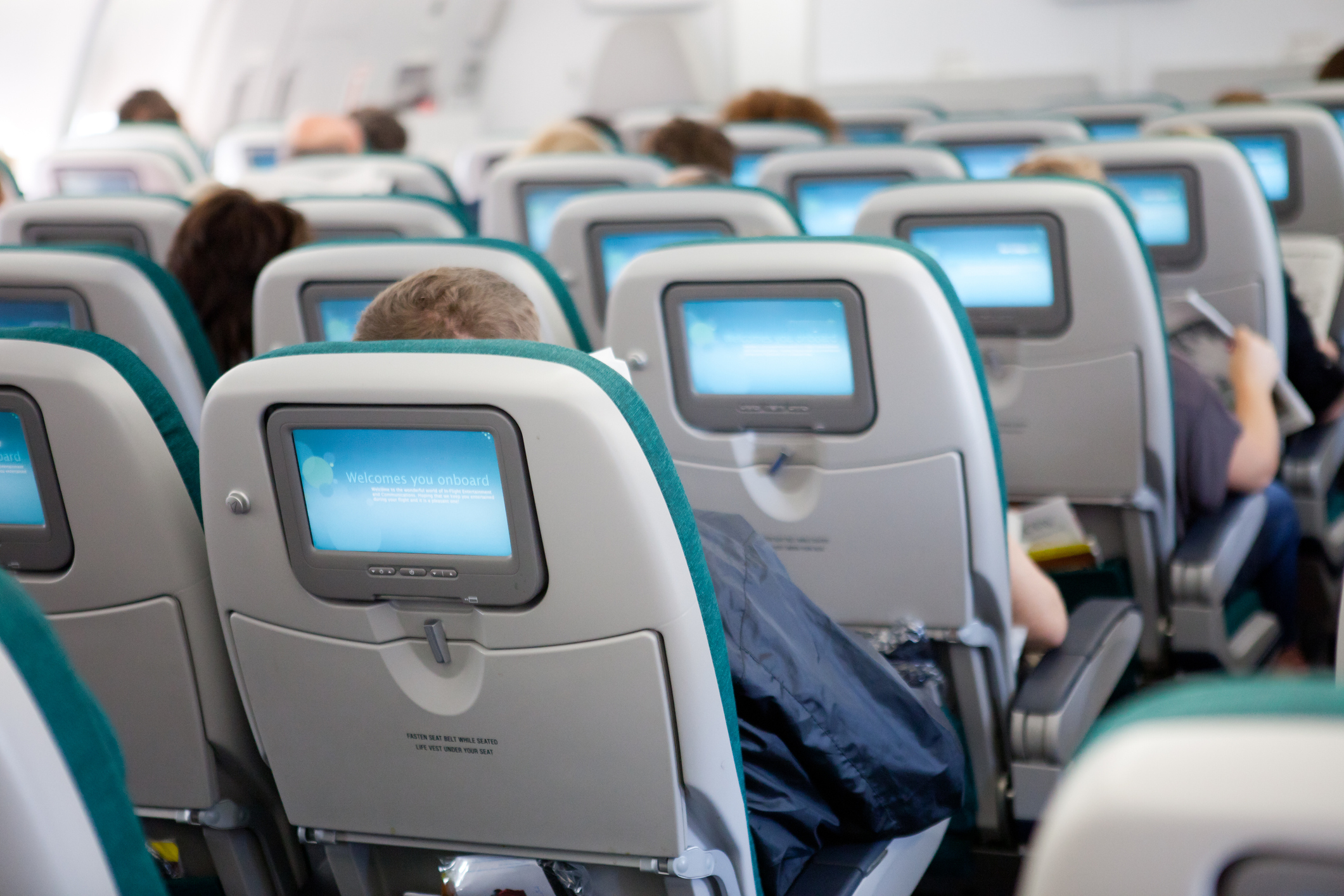 New York, USA - August 7, 2011: Modern airplane seat with individual monitors displaying flight information from the onboard computer.